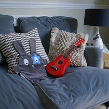 The Doudoods grey + blue star style baby comforter on grey sofa with toddler guitar