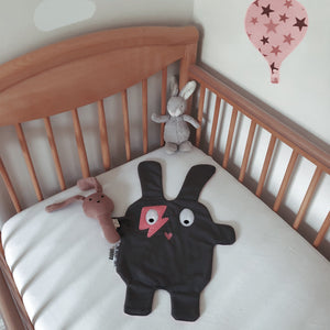 The Doudoods grey + pink flash style baby comforter lying flat in wooden baby cot