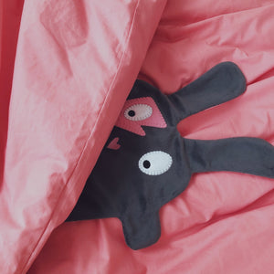 The Doudoods grey + pink flash style baby comforter peeking out of pink sheets in a bed