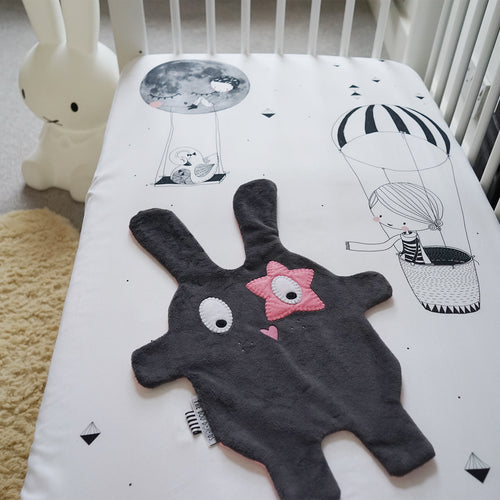 The Doudoods grey + pink star style baby comforter laid flat on toddler cot bed