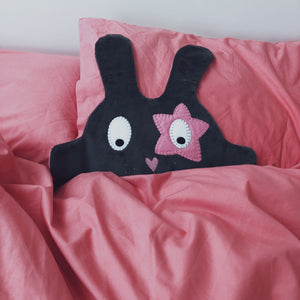 The Doudoods grey + pink star style baby comforter peeking out of pink bedding
