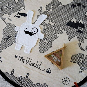 The Doudoods white + black monocle style baby comforter laid flat on world play rug