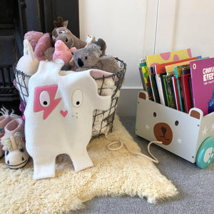 toddler room with white + pink Doudoods Flash baby comforter on toy basket next to book box
