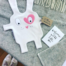 White + pink Doudoods heart baby comforter with grey blanket and welcome to the world card