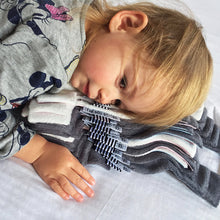 Toddler snuggling a stack of Doudoods baby comforters