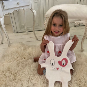 Toddler girl playing with a The Doudoods white + pink heart style baby comforter
