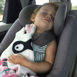 Toddler sleeping in car seat with white + black Doudoods bandit baby comforter