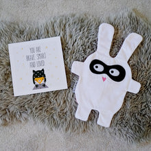The Doudoods white + black Bandit style baby comforter on rug with be brave card