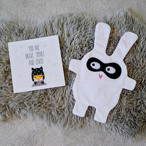White Bandit style Doudoods baby comforter on rug with brave card