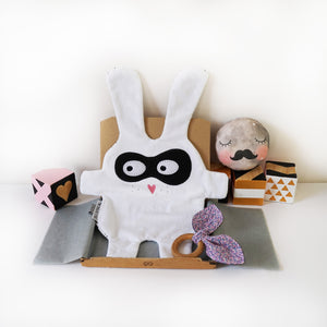 The Doudoods white + black bandit style baby comforter displayed with liberty wooden teething ring