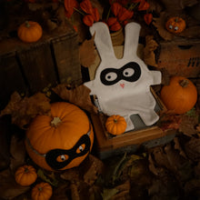 The Doudoods white + black bandit style baby comforter in halloween setting with pumpkins and dress up superhero mask