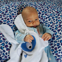 Newborn cuddling The Doudoods white + blue heart style baby comforter lying on blue muslin