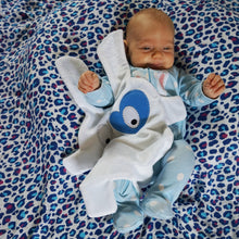 Newborn playing on floor with The Doudoods white + blue heart style baby comforter