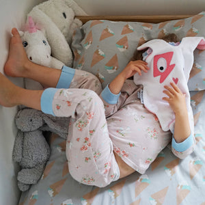 Toddler girl playing with her The Doudoods white + pink flash style baby comforter on her bed