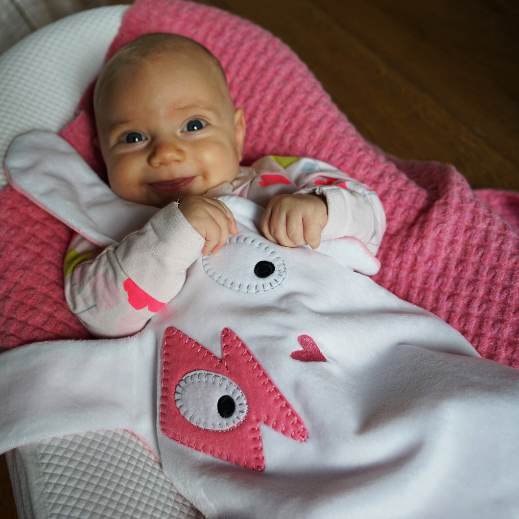 The Doudoods white + pink flash style baby comforter on smiling baby's tummy