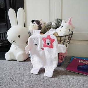 The Doudoods white + pink star style baby comforter drapped on toy basket with Miffy lamp on floor