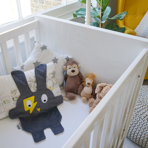 The Doudoods grey + yellow flash style baby comforter in baby crib
