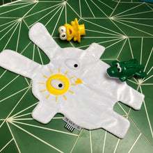 The Doudoods white + yellow sunshine style baby comforter laid flat on bathroom floor