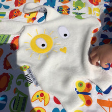 White + yellow Sunshine Doudoods baby comforter on kids towel