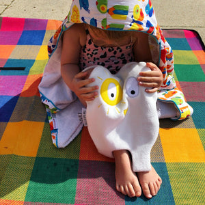 Toddler cuddling The Doudoods white + yellow sunshine style baby comforter on picnic blanket in sunshine
