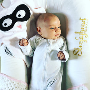 Newborn baby lying in sleepyhead with The Doudoods white + black bandit style baby comforter