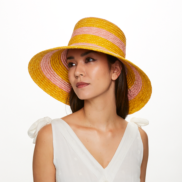 Brunette model wears Eugenia Kim Annabelle straw sunhat in Marigold/Pink stripe
