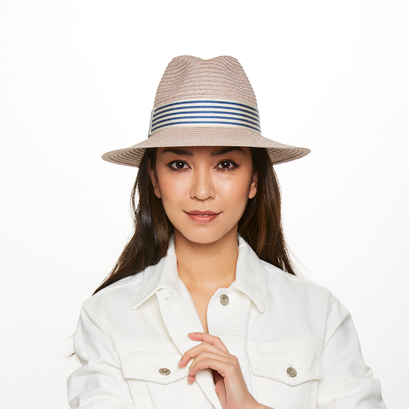 Model wearing the Courtney packable fedora in stone with blue/ivory band from the Eugenia Kim Resort 2020 Collection.