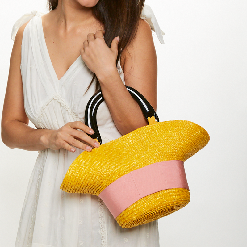Model holding Eugenia Kim Evie bag in Marigold with Pink grosgrain
