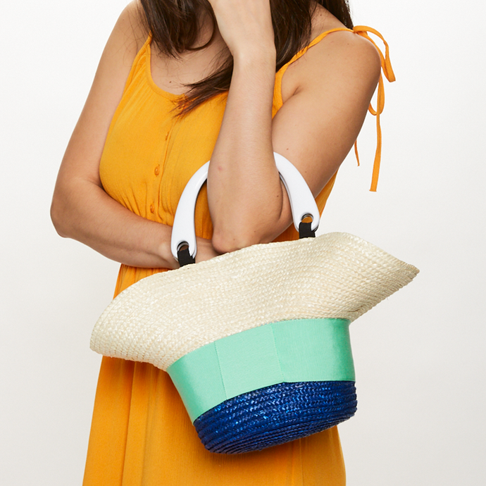Model holding Eugenia Kim Evie bag in Ivory/Cobalt with Mint grosgrain band