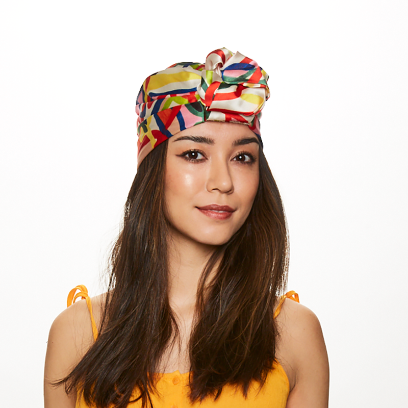 Brunette model wearing Eugenia Kim Gigi satin scribble print headscarf