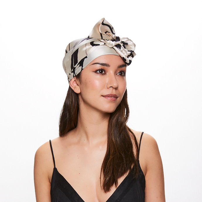 Brunette Model wearing Eugenia Kim Gigi satin headscarf with Ivory/Black floral print motif