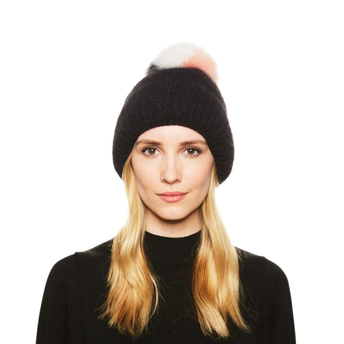 Female model with blonde hair wears the Eugenia Kim Maddox angora knit beanie in Black with Pink/Black/White fox fur pom