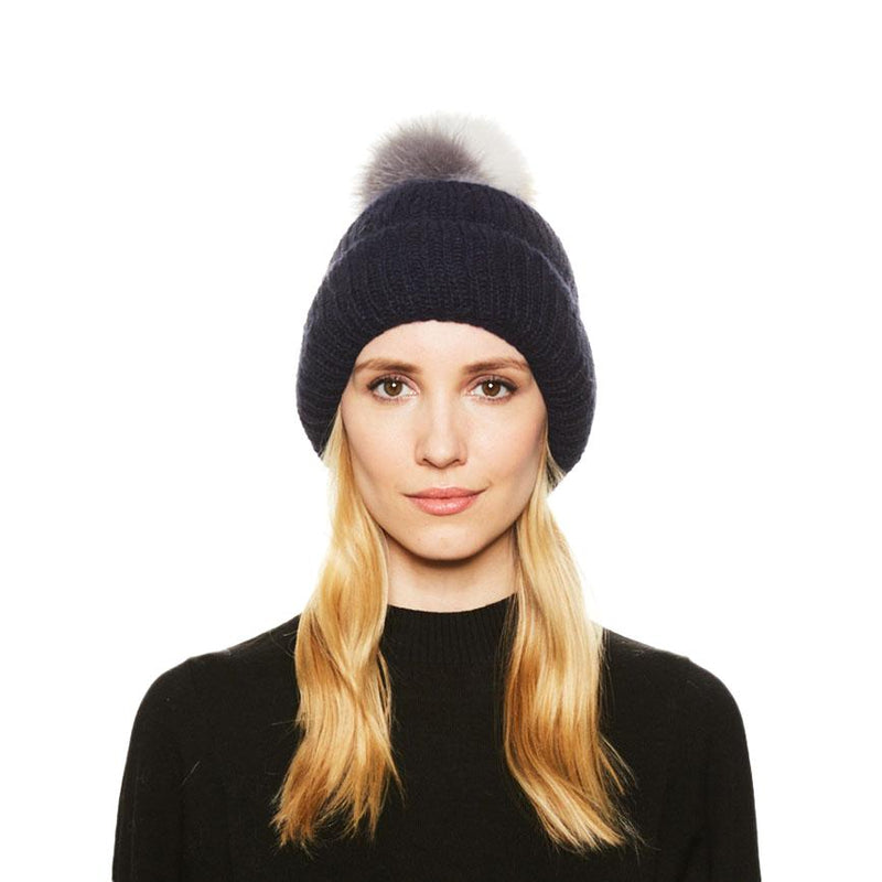 Female model with blonde hair wears the Eugenia Kim Maddox angora knit beanie with Camel/White/Gray fox fur pom.