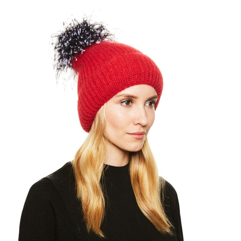 Model with blonde hair wears the Eugenia Kim angora knit Maddox beanie in red with black and white ostrich pom