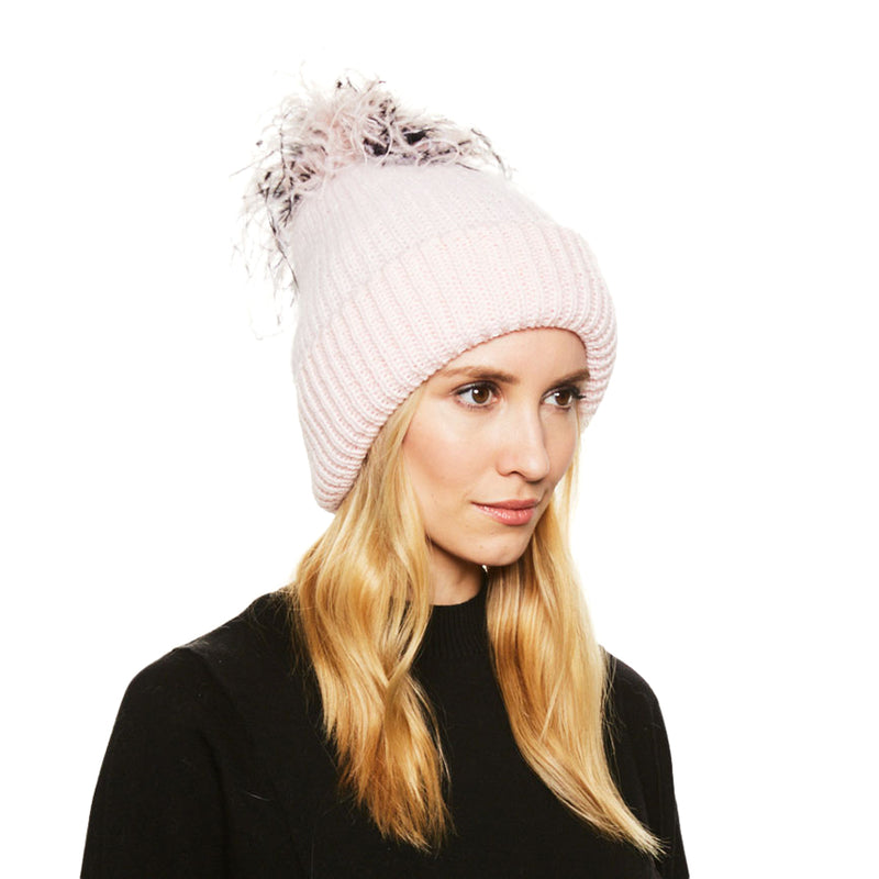 Model wears Eugenia Kim Maddox angora knit beanie in Pale Pink with blush/black/white ostrich pom