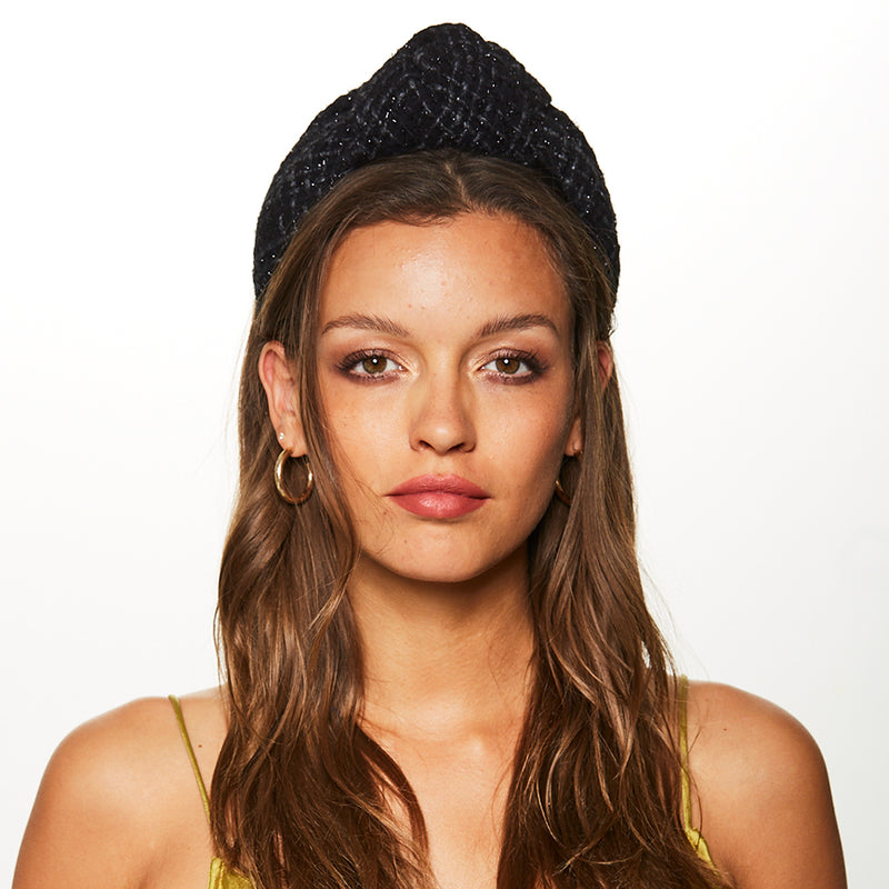 Model wearing the Maryn black metallic boucle headband by accessories designer Eugenia Kim