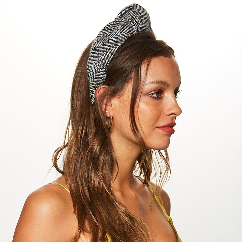 Side view of Model wearing the knotted black/white houndstooth boucle headband by accessories designer Eugenia Kim