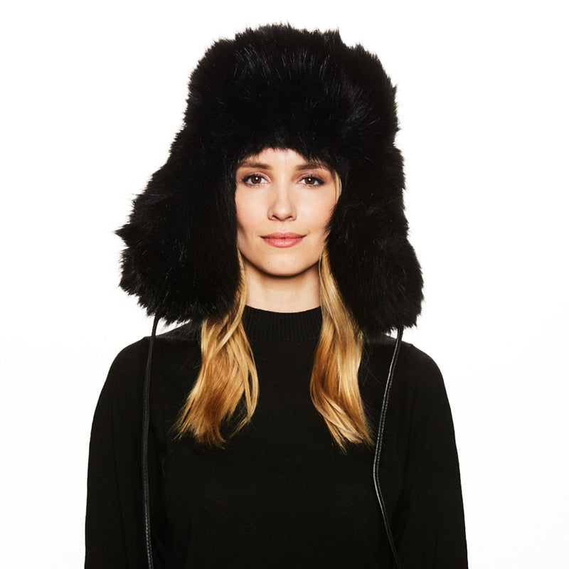 A female blonde haired model wearing the Eugenia Kim Owen Trapper in Black Faux Fur
