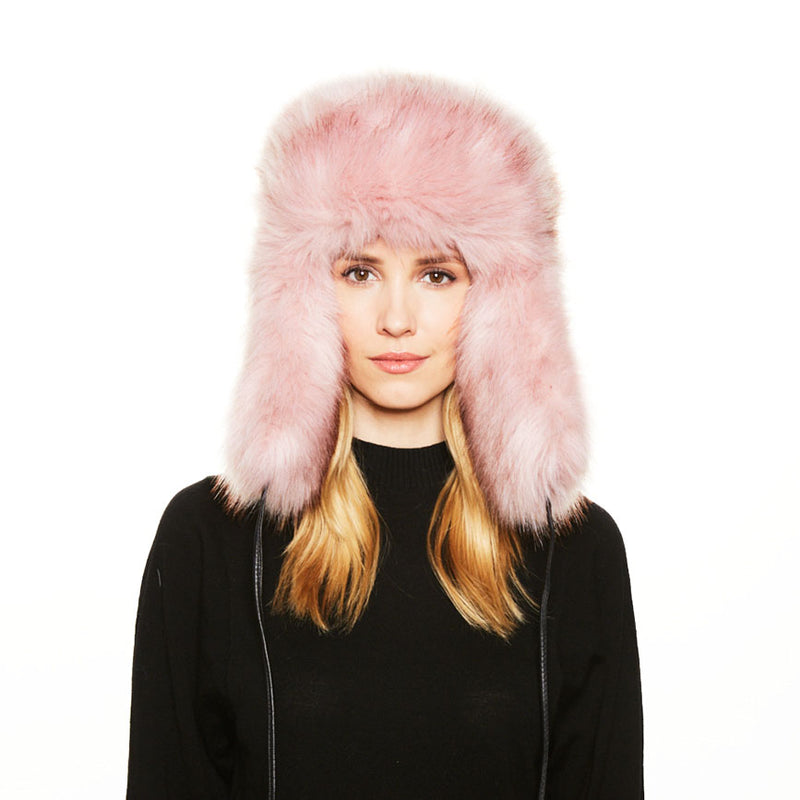A female model with blonde hair wears the Eugenia Kim Owen Trapper in Pink Faux Fur