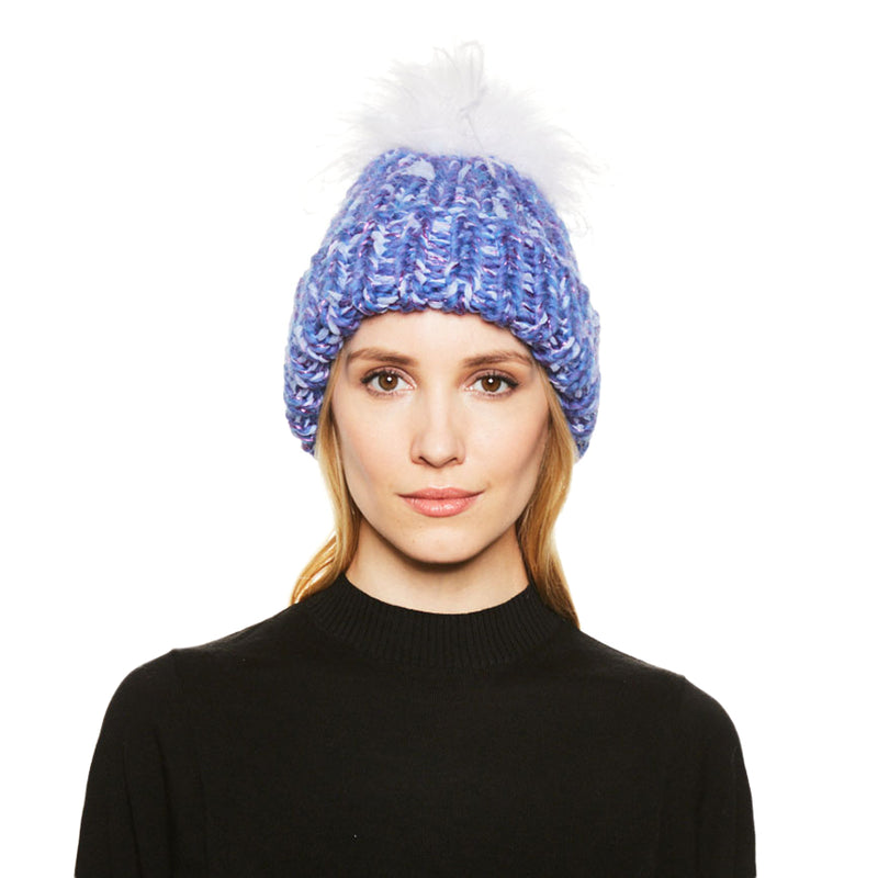 A blonde haired female model wears the Eugenia Kim hand knit Rain beanie in Periwinkle with White ostrich pom