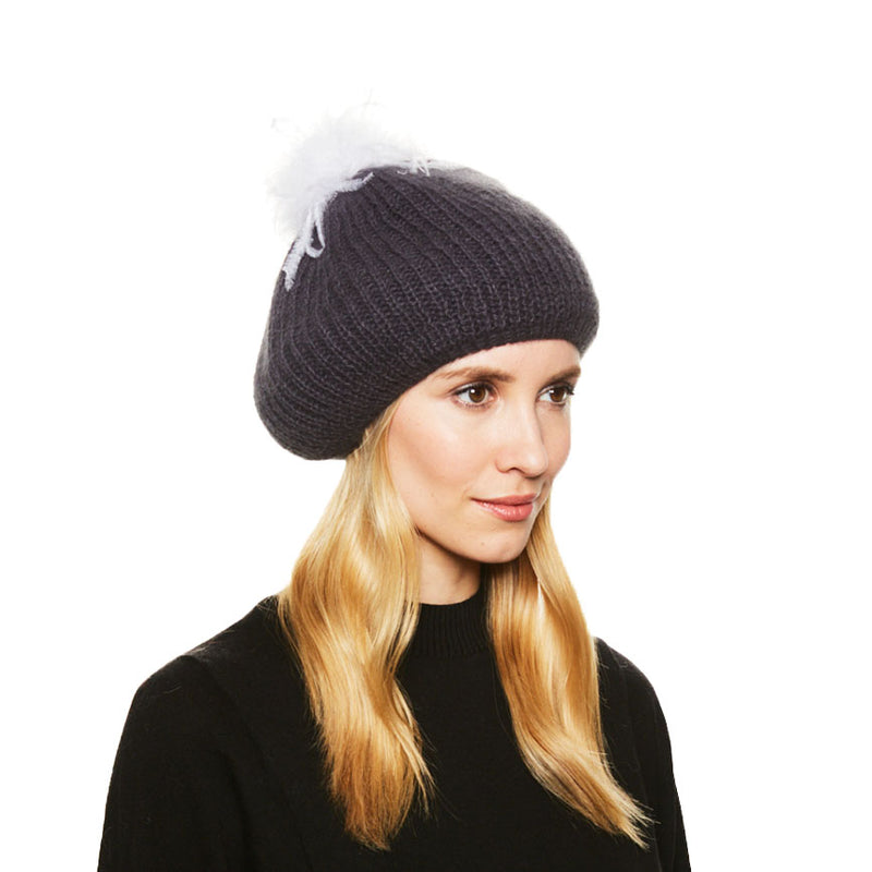 A model with blonde hair wears the Eugenia Kim angora knit Rochelle beret in Charcoal with winter white Ostrich feather pom