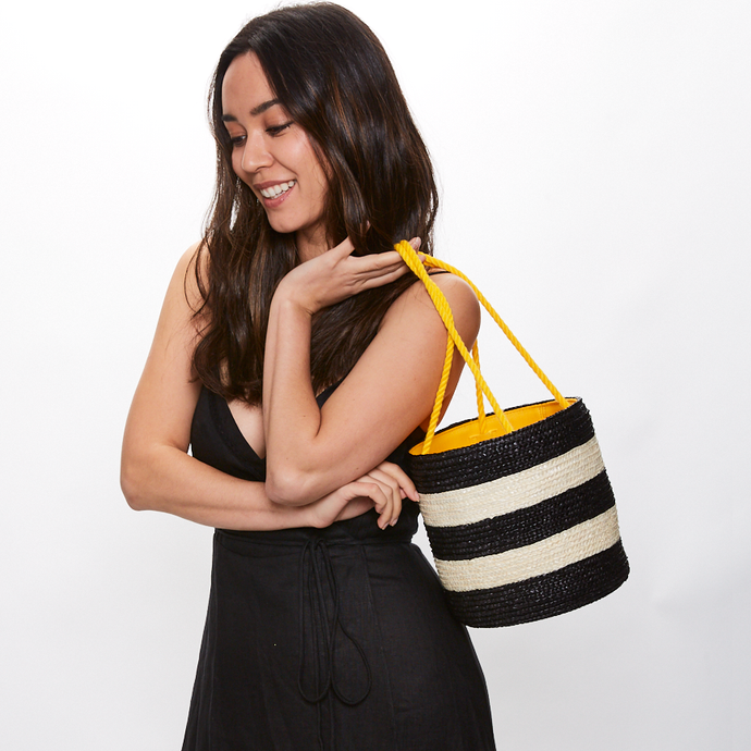 Model holding Eugenia Kim Robbie bucket bag in Ivory/Black Stripe