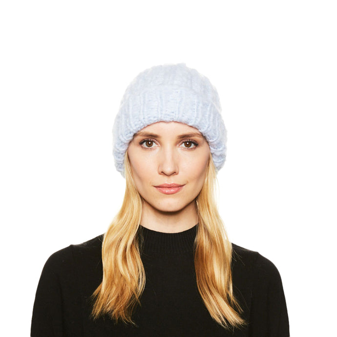 A blonde female model wears the Eugenia Kim brushed Cashmere Shannon Knit Beanie in Ice Blue