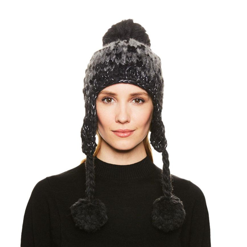 A blonde haired female model wears the Eugenia Kim Skye wool knit trapper hat in gray ombre leopard print