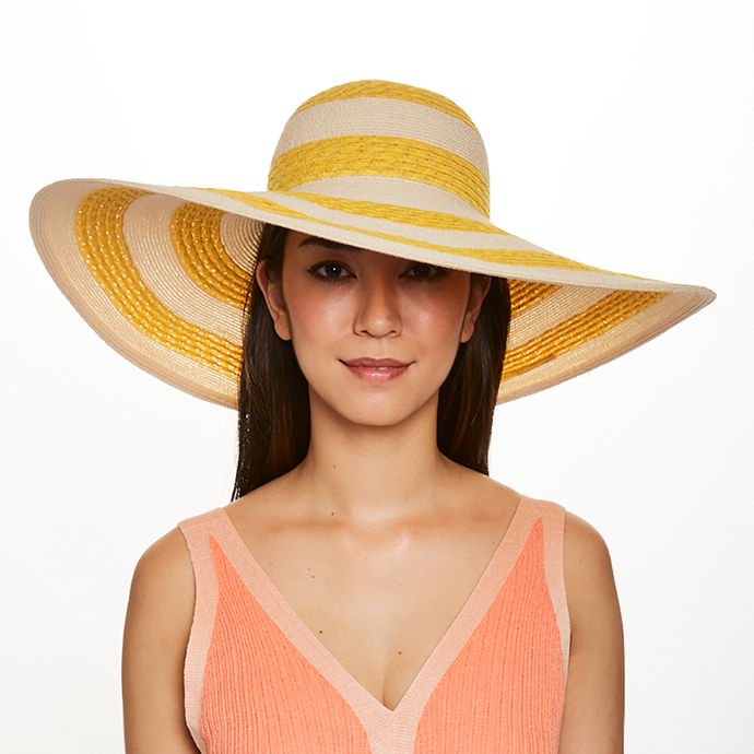 Brunette model wearing Eugenia Kim Sunny striped straw sunhat in Yellow/Ivory
