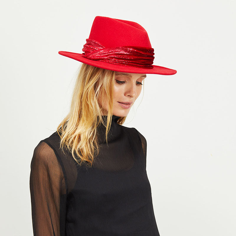 A white female model with blonde hair wearing the Eugenia Kim Red Blaine fedora