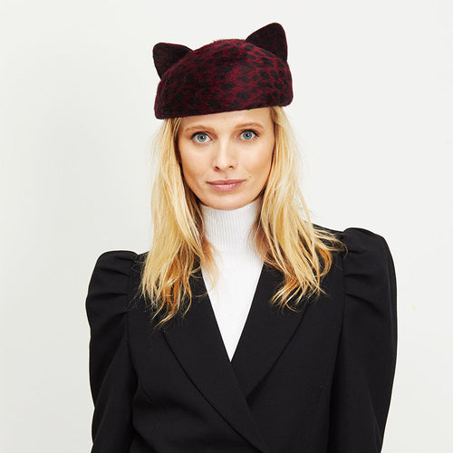Female model with blonde hair wearing Eugenia Kim Caterina cat-ear beret in red leopard print