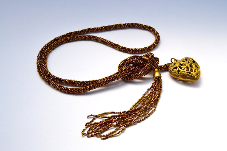 THICK GOLD BEAD WRAP TIED BOTTOM NECKLACE W CARVED HOLLOW HEART & MULTIPLE GOLD STRAND TASSELS