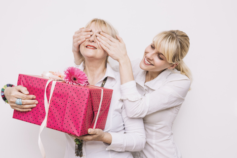 daughter surprising her mother with a gift