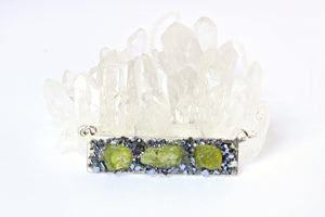 Peridot crystal jewelry necklace atop a white crystal background